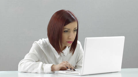 young woman working with white laptop: studio shot with gray background Live Action