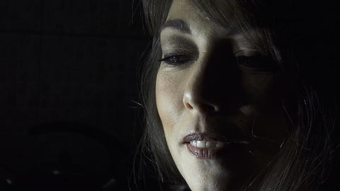 smiling woman in the darkness: half face lighted , Rembrandt lighting Live Action