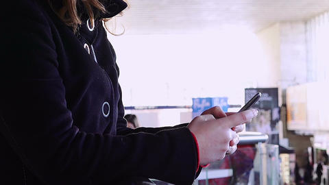 hands of woman using a smartphone with people and shops in background Footage