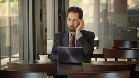 businessman answering at the mobile phone while working in a cafeteria Footage