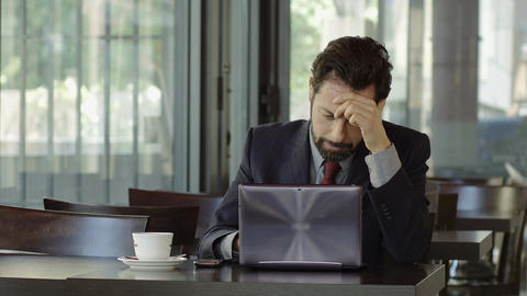 troubled and worried businessman sitting with laptop and a cup of coffee Footage