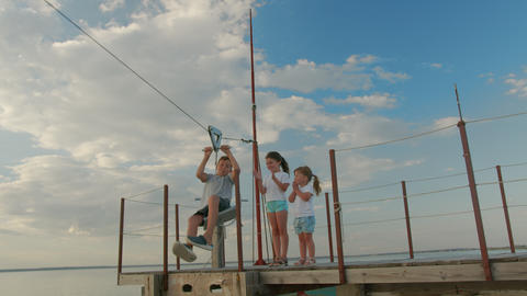 Three children, having fun on a swing in the backyard on sunset Live Action