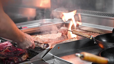 Chef grilling delicious meat steaks in commercial kitchen Live Action