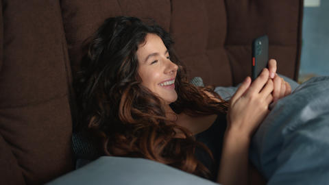 Happy woman using mobile phone in bed. Cheerful girl looking cellphone screen Live Action