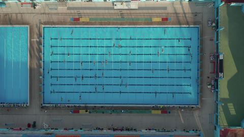 Swimmers training doing Laps in Blue Pool, Epic Birds Eye Perspective in Live Action