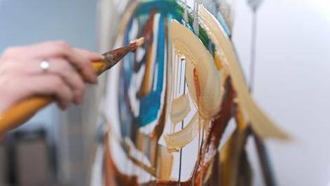 Artist paints creative painting with passion in a studio 2 Live Action