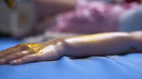 Pouring the glowing sparkles to the womans hand for bodyart project 2 Live Action