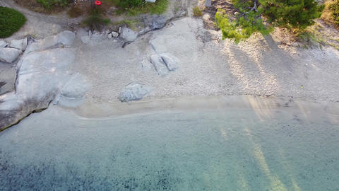 Beach with white sand clear blue tranquil sea and walking path. bird aerial view Live Action