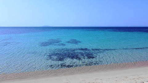 Clear empty sand beach and transparent turquoise sea. Exotic tropic vacation destination. Aerial Live Action