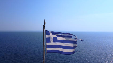 Greek flag flutters in the wind with the blue open sea and blue sky behind Live Action