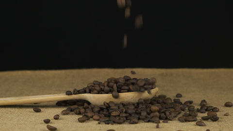 Coffee grains fall into a wooden spoon and heap is poured. Slow motion Live Action