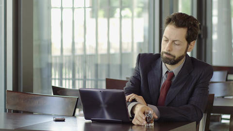 depressed businessman drinking alcohol during work; laptop, cafeteria, table Footage
