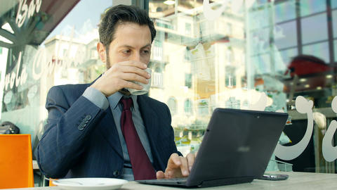 businessman taking coffee and working with a laptop: drinking coffee Footage
