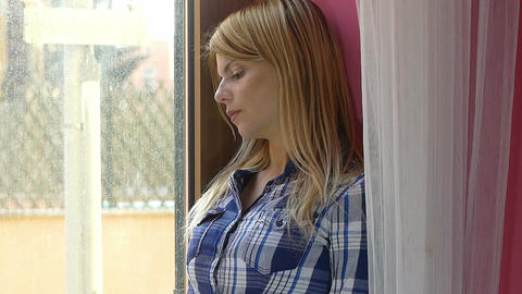 sad woman portrait: depressed young woman looking out of the window Footage