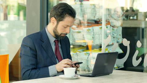 businessman at work sitting at the table of a cafeteria using smartphone Footage