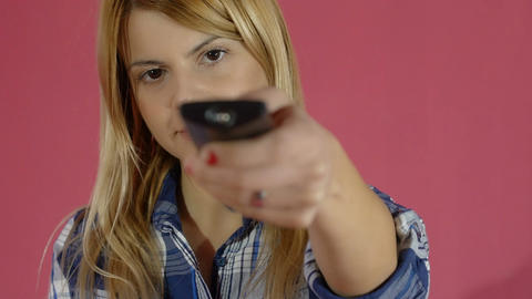 young woman using tv remote control to change tv programs Footage