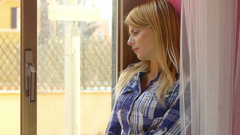 sad and depressed young woman standing near the window and looking out Footage