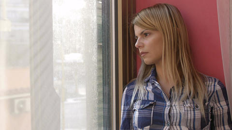 sad and lonely young woman looks out of the window: depressed woman Footage