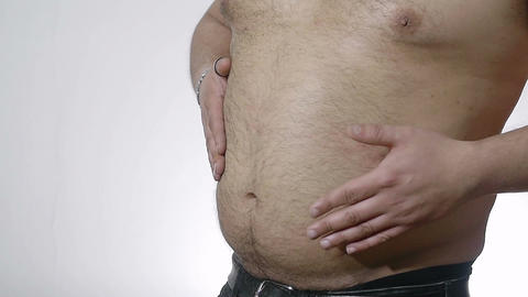 fat man hitting his belly with hands: overweight, obesity, diet, healthcare Live Action