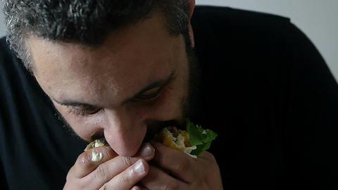 young man eating hamburger: junk food, diet, obesity, healthcare ビデオ