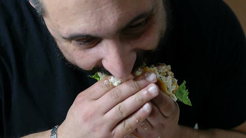 young man eating hamburger: junk food, diet, obesity, healthcare Live Action