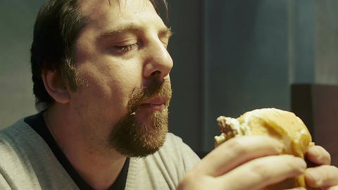 hungry man eating hamburger: closeup footage of man eating Footage