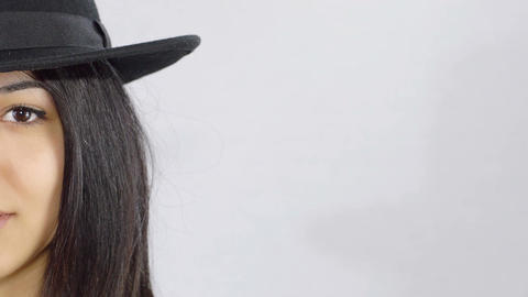 beautiful and bright woman wearing hat: half face portrait on white background Live Action