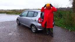 Funny pumpkinhead guy in bright red cloak, clutch head in panic gesture Live Action