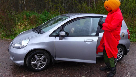 Man wear Halloween pumpkin on head and red rainsuit, come out small car Footage
