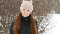 Woman portrait in snowfall, lady look straight to camera with faint smile Footage