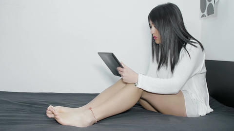 young woman using a tablet computer on the bed and typing on its touchscreen Footage