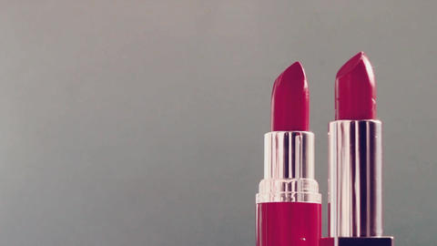 Two pink lipsticks and shining light flares, luxury make-up product and holiday Live Action