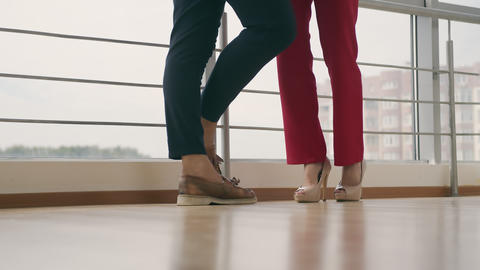 Legs of a man and a woman approaching each other indoors. Man and woman go to Live Action