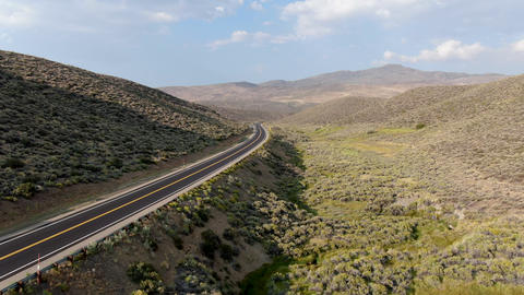 Aerial view of scenic road in the middle of green desert valley in Mono County Live Action