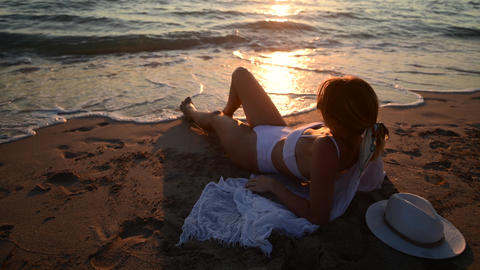 Young woman come to water on sunset at sandy beach, island holidays Live Action