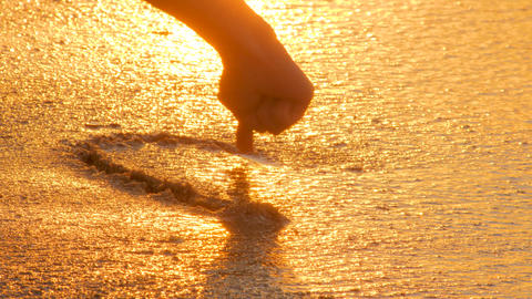 Love theme. Symbol of love. Sunset, sea background. Heart on sand washed by sea. Instability concept Live Action