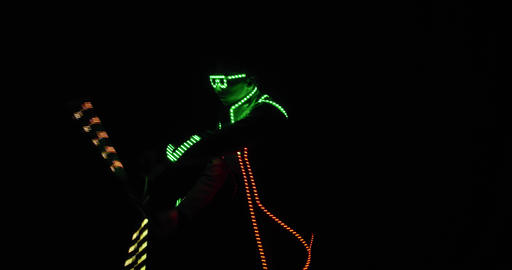 Man in glowing clothes and glowing glasses is dancing in the dark, show, 4k Live Action