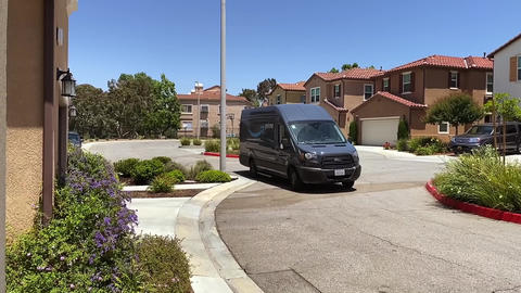 Amazon delivery van, driving through neighborhood of homes with packages Live Action