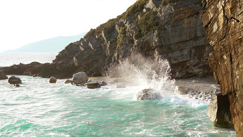 Surf Spray on a Wild Rocky Beach. Slow Motion Live Action