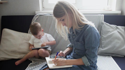 Young woman working from home with little child. Mother is working while her son Live Action