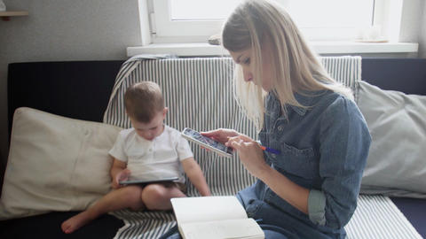 Young woman working from home with little child. Mother is working with phone Live Action