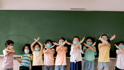 Group of diverse young students wear mask and standing together in classroom Live Action