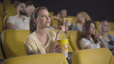 Portrait of engrossed Caucasian woman watching exciting film in cinema and Live Action