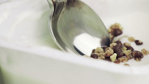 close-up of healthy cereal and chocolate and white yogurt on the spoon, concept of Live Action