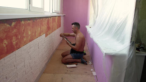 A young man sitting on the floor smears the mortar on the tiles Live Action