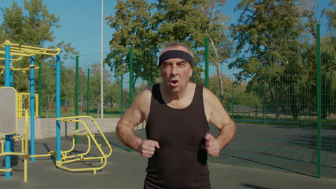 Elderly man doing exercise. Senior man running in park. health lifestyle and Live Action