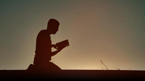 Man reading religious book at evening Live Action