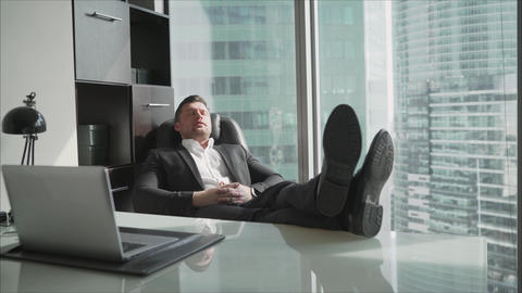 A businessman in his office throws his feet on the table. Exhausted businessman Live Action