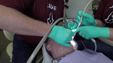 Dentist and assistant dental work male patient HD 995 Footage