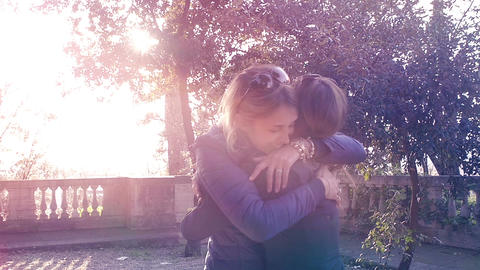 old friends hugging each other in a park: happy female friends Live Action